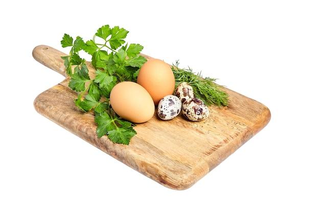 木製のまな板に鶏と斑点のあるウズラの卵。緑のパセリとディル。