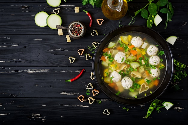 Куриный и овощной суп с фрикадельками, цуккини и пастой. квартира лежала. вид сверху