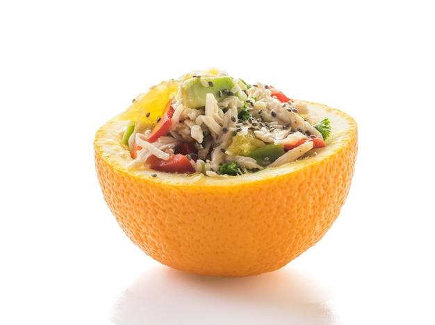 白い表面に分離された半分オレンジのチキン、アボカド、ピーマンのサラダ。トロピカルフルーツとチキンのダイエット食品。