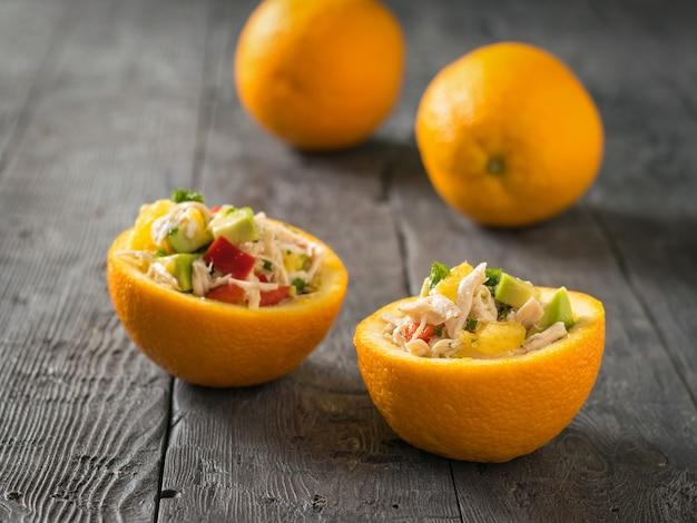 Салат из курицы, авокадо и апельсина в двух половинках апельсина на фоне целых апельсинов. диетическое питание из тропических фруктов и курицы.
