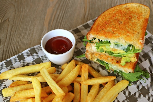 Chicken avocado salad sandwich and french fries served on wooden table