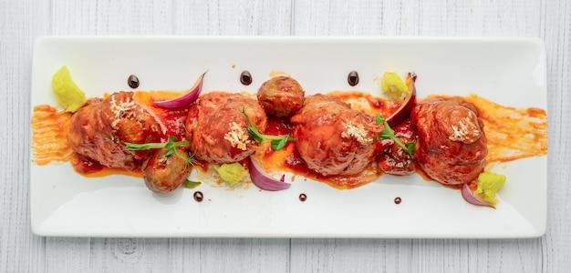 나무 테이블에 야채와 토마토 소스에 구운 닭