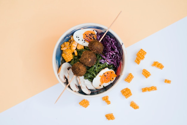 Chicken balls in stick over the bowl with salad and eggs on dual background