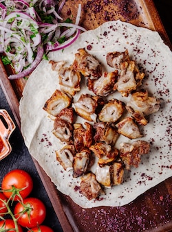 Chicken barbecue in lavash bread with salad and herbs.