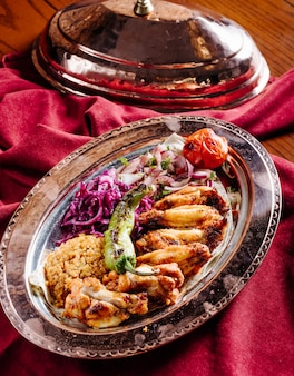 Chicken barbecue with rice garnish and vegetable salad inside ethnic plate.