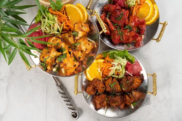 Шашлык из курицы, говядины и свинины с овощным гарниром и пряными специями, приготовленный в тандыре. набор из трех горячих мясных блюд в традиционных индийских тарелках.