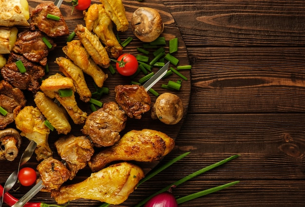 Chicken and beef skewers on a wooden table with tomatoes and green onions.