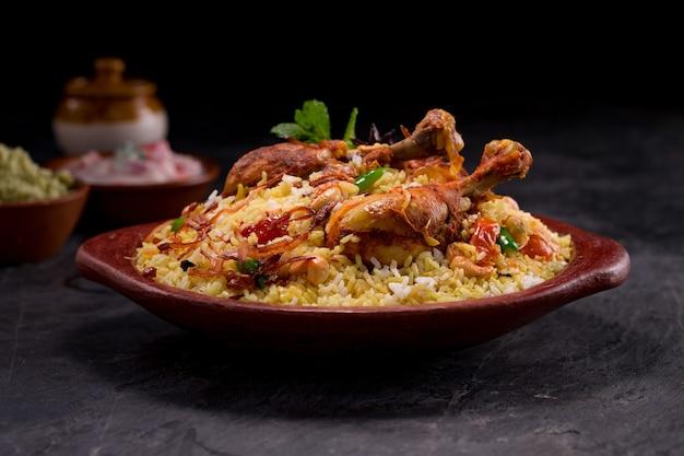 Курица бирияни с рисом джира, выложенная в глиняной посуде с раитой на сером фоне