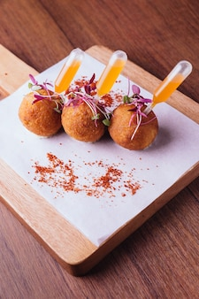 Chicken biryani arancini served in rice ball.