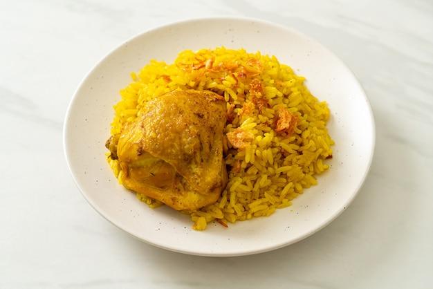 チキンビリヤニまたはカレーライスとチキン-インドのビリヤニのタイ-イスラムバージョン、香りのよい黄色いライスとチキン-イスラム教徒の料理スタイル