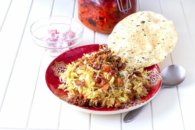 Chicken biryani served with yogurt tomato raita and achar indian food white background