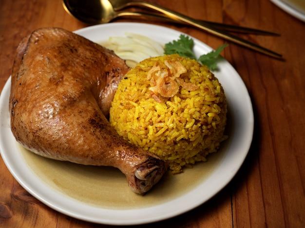 레스토랑의 나무 테이블에 향신료에 절인 쌀과 치킨 비리 야니