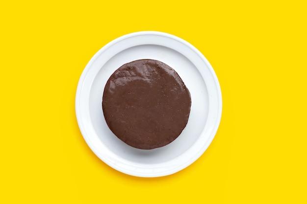 黄色の背景に白いプレートの鶏血豆腐。