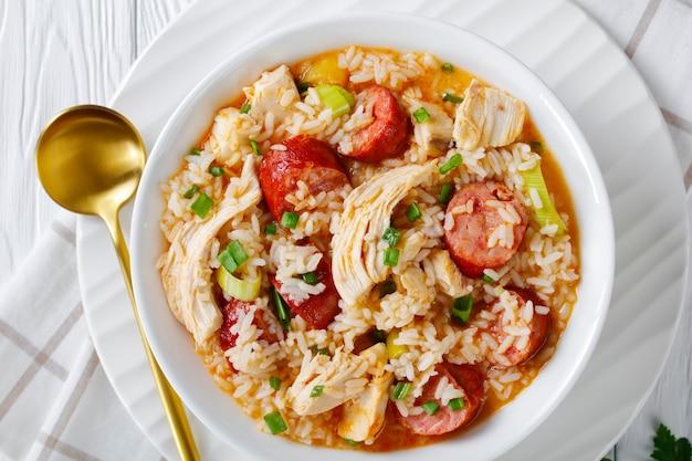 Тушеное мясо из куриного болота с копченой колбасой и луком-пореем, приготовленное в курином бульоне, подается на белой тарелке, посыпанной зеленым луком