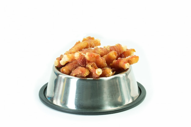 Chicken bone in stainless bowl for dog isolated. snack for pets concept.