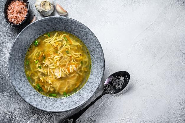 Куриный бульонный суп с луком-пореем, морковью, лапшой, зеленым луком и петрушкой. вид сверху.
