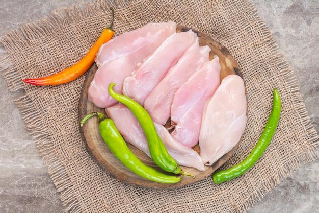대리석에 삼 베에 보드에 닭 가슴살과 후추.