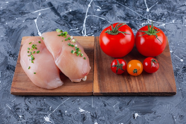 Куриная грудка и помидоры на доске на синей поверхности
