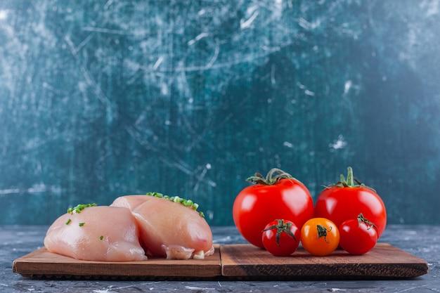 파란색 표면에 보드에 닭 가슴살과 토마토