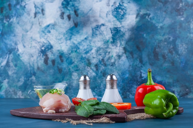 まな板の上の鶏の胸肉と野菜、青い表面の黄麻布ナプキン