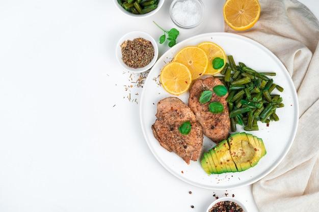 Куриная грудка, авокадо и стручковая фасоль с базиликом на плоской тарелке на светлом фоне. здоровая пища. вид сверху, горизонтальный, с местом для копирования.