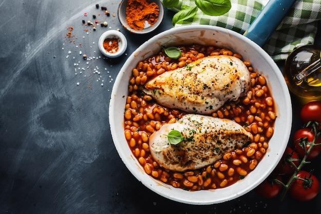 Chicken breast cooked or stuffed with beans in tomato sauce on pan.
