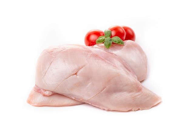 Филе куриной грудки, украшенное помидорами и базиликом на белом фоне.