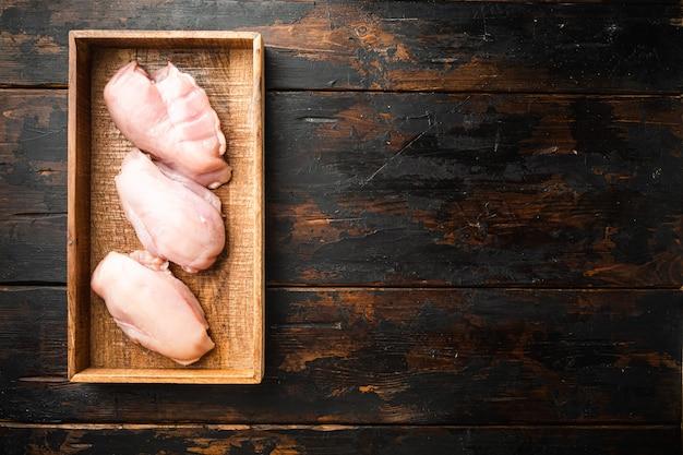 오래된 어두운 나무 탁자에 있는 나무 상자에 있는 닭 가슴살 필레 세트