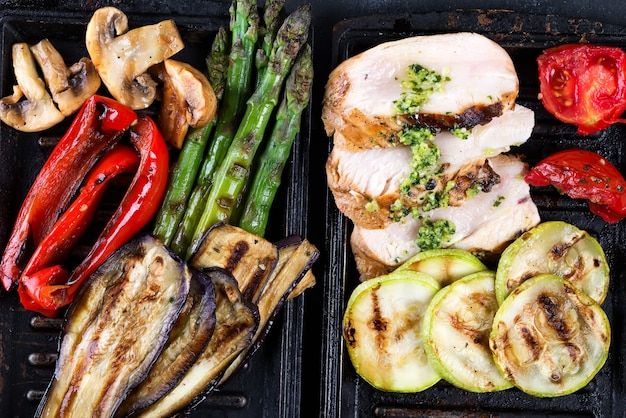 Chicken breast grill with bbq vegetables and pesto sauce in a cast iron pan close up