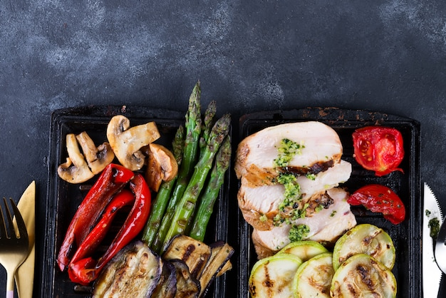Chicken breast grill with bbq vegetables and pesto sauce in a cast iron pan on concrete