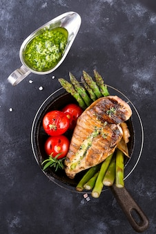Chicken breast grill with bbq vegetables and pesto sauce in a cast iron pan on a stone
