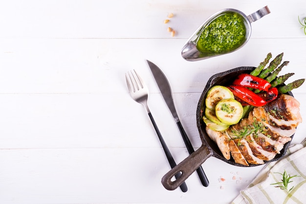 Chicken breast grill with bbq vegetables and pesto sauce in a cast iron pan on white