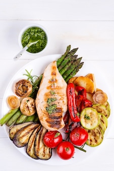 Chicken breast grill with bbq vegetables and pesto sauce in a plate on wood