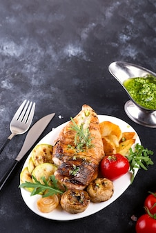 Chicken breast grill with bbq vegetables and pesto sauce in a plate