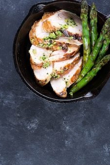 Chicken breast grill with green asparagus and pesto sauce in a cast iron pan