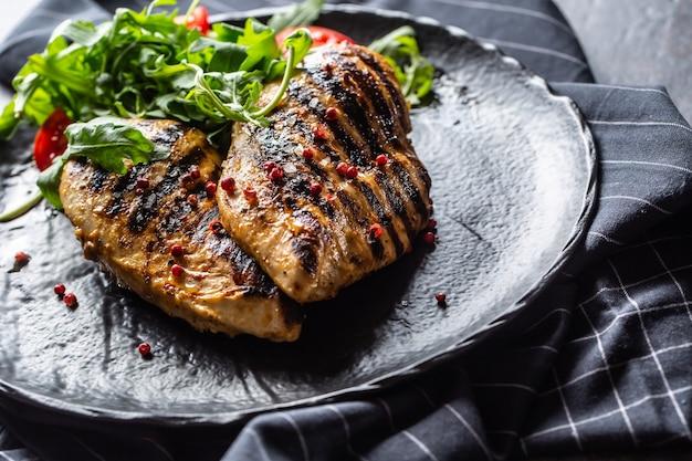 Куриная грудка на гриле со специями, перцем, солью, помидорами и рукколой.