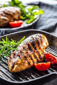Куриная грудка на гриле со специями, перцем, солью, помидорами и розмарином.