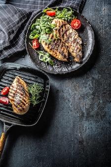 Куриная грудка на гриле со специями, перцем, солью, помидорами, розмарином и рукколой - вид сверху.