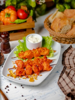 Chicken breast pieces sish kebab, grilled and served with cream sauce, sumakh and lettuce