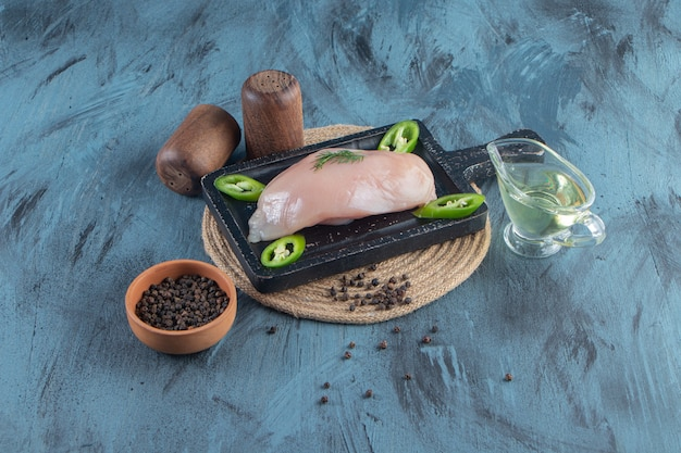 Chicken breast and sliced pepper on a board on a trivet next to spice and oil bowls, on the blue surface.