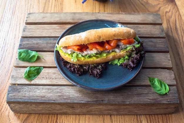 Копченый лосось с куриной грудкой на сэндвиче из ржаного хлеба на деревянном столе