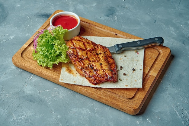 Chicken breast steak in spices on a wooden board on a gray concrete table. healthy food