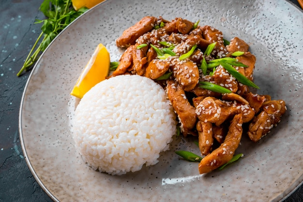 Chicken breast teriyaki with rice and sesame seeds close up, traditional asian food
