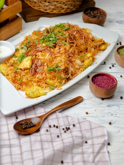Chicken breast, tomato sauce rice, risotto, plov with herbs , yogurt and sumakh in white plate