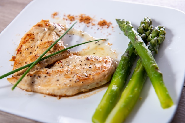 Chicken breast with fresh asparagus on white plate