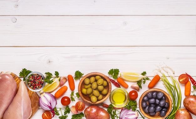 Куриная грудка со свежими овощами и специями для приготовления.