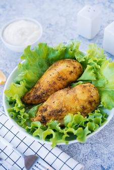 저녁 식사를 위한 신선한 허브와 함께 향신료와 기름으로 구운 닭 가슴살, 밝은 배경의 건강한 음식, 선별적인 집중 프리미엄 사진