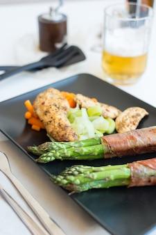 ベーコンに包まれたアスパラガスを入れた鶏の胸肉ステーキ
