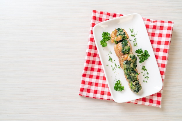 접시에 시금치와 치즈로 채워진 닭 가슴살