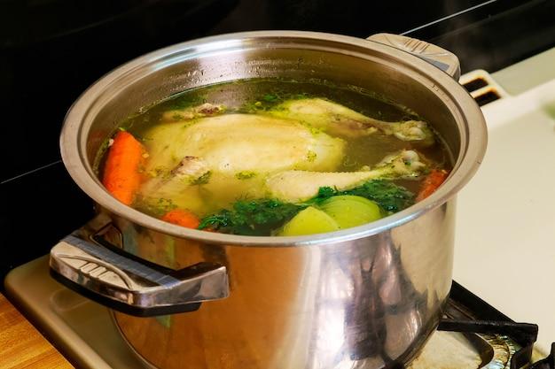 Куриный бульон, морковь, курица зеленая куриный суп в миске с сухариками.